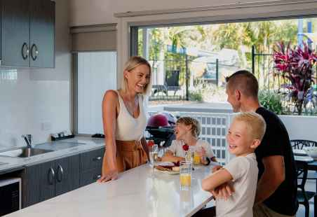 Family enjoying a meal in the Poolside Penthouse Kitchen