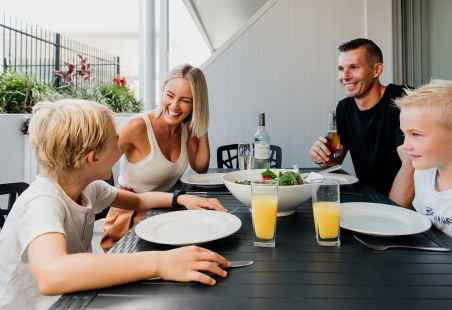 Family enjoying a meal in the Poolside Penthouse Alfresco area